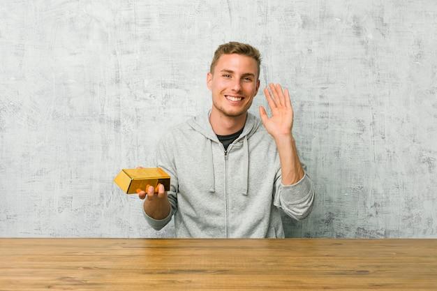 たくさん笑ってうれしそうなテーブルに金塊を保持している若いハンサムな男