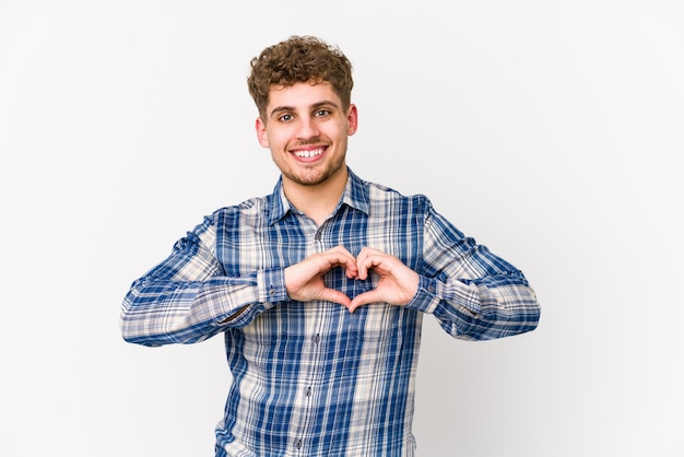 若いブロンドの巻き毛の白人男性の笑みを浮かべて、手でハートの形を示します。