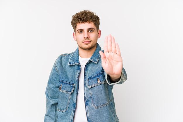 Человек молодого белокурого вьющиеся волосы кавказский стоя при протягиванный знак стопа показа руки, предотвращая вас.