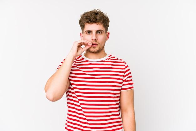 Молодой белокурый вьющиеся волосы кавказских человек с пальцами на губах, сохраняя в тайне.