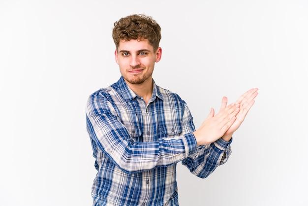 エネルギッシュで快適な感じの若いブロンドの巻き毛の白人男性は自信を持って手をこすります。