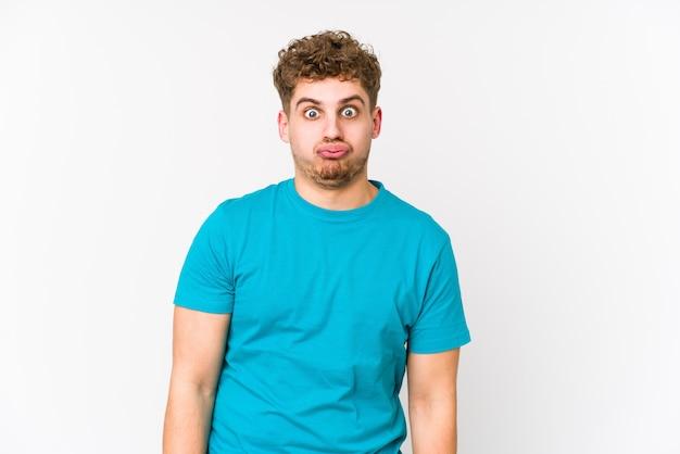 若いブロンドの巻き毛の白人男性は頬を吹く、疲れた表情をしています