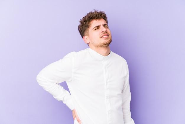背中の痛みに苦しんでいる若いブロンドの巻き毛の白人男性。