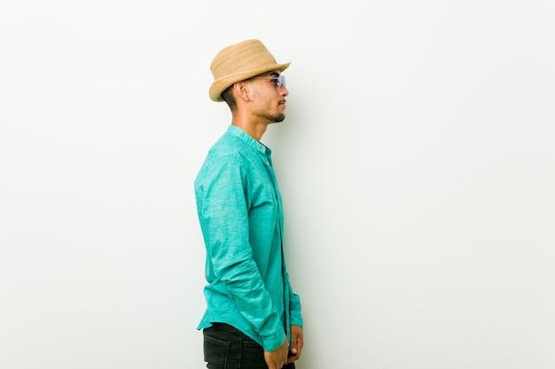Молодой латиноамериканский человек в летней одежде, глядя влево