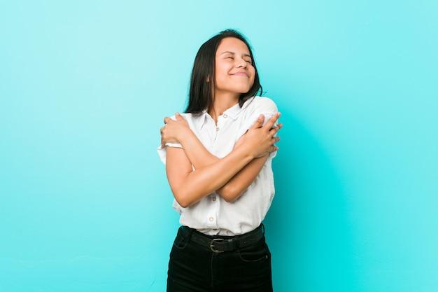 青い壁に対して若いヒスパニックのクールな女性が抱擁します。
