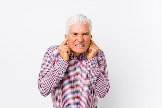 Старший кавказский человек, охватывающих уши руками.