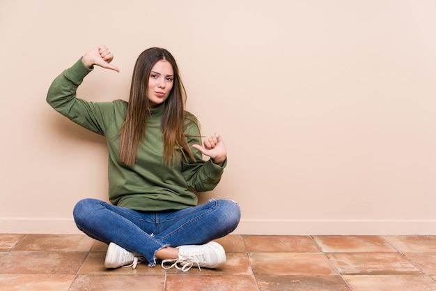 床に座っている若い白人女性は誇りに思って、自信を持って、次の例です。