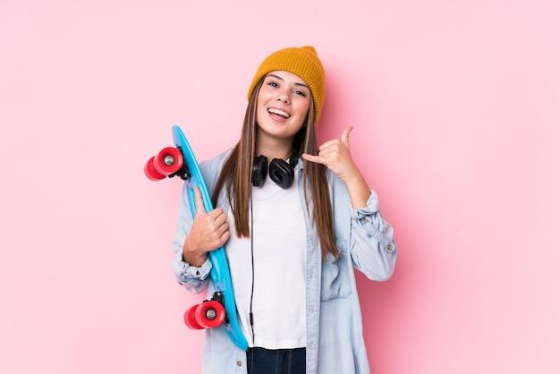 Молодая женщина конькобежца держа коньк показывая жест звонка мобильного телефона с пальцами.