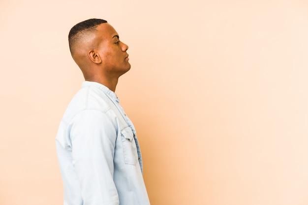 Молодой латиноамериканец на бежевой стене смотрит влево