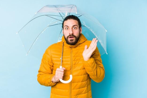 Молодой человек носить длинные волосы взгляд, держа зонтик удивлен и шокирован.