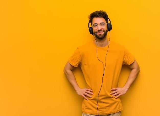 Молодой человек слушает музыку с руки на бедрах