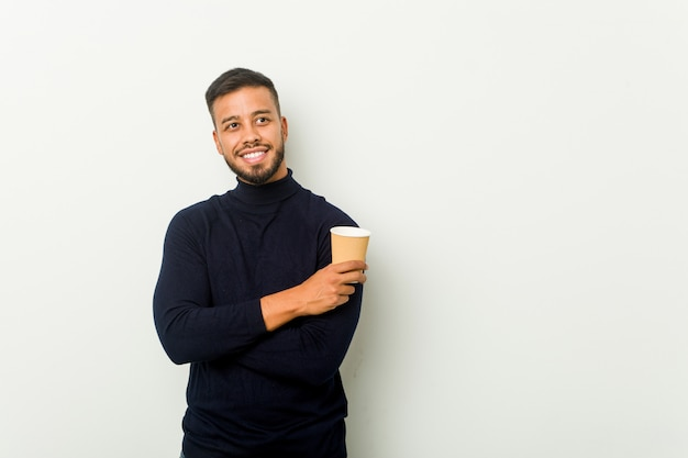 Молодой смешанной расы азиатских человек, держащий на вынос кофе улыбается уверенно со скрещенными руками.