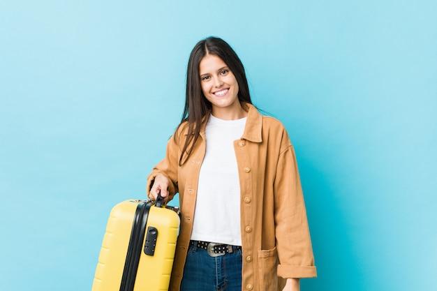 Молодая кавказская женщина держа чемодан счастливый, усмехаться и жизнерадостный.