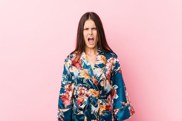Молодая кавказская женщина нося пижаму кимоно кричащую очень сердитую и агрессивную.