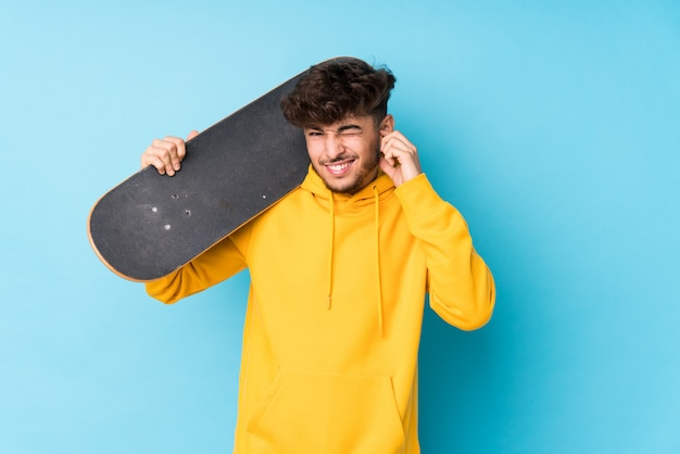 Молодой скейтер человек, охватывающих уши руками.