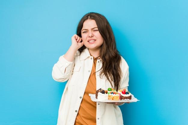 Молодая женщина, держащая сладкие торты, охватывающих уши руками.