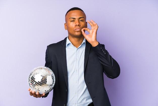 秘密を守る唇に指でボールパーティーを保持している若いラテン男。