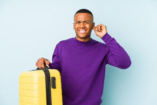 Молодой путешественник мужчина держит чемодан, охватывающих уши руками.