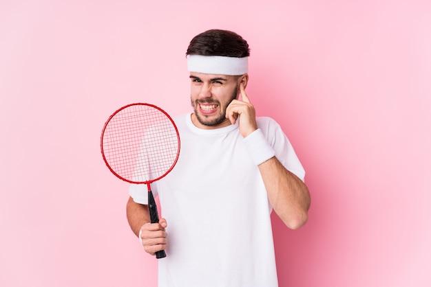 Молодой человек кавказской, играть в бадминтон, охватывающих уши руками.