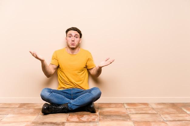 ジェスチャを疑って肩を疑い、肩をすくめ床に座っている若い白人男。