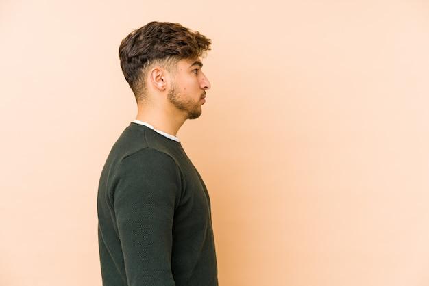 Молодой мужчина на бежевой стене смотрит влево