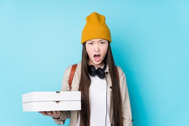 Молодая китайская женщина держит пиццу кричать очень злой и агрессивный.