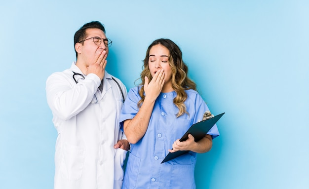 Молодые пары доктора представляя в голубой стене зевая показывая утомленный жест покрывая рот рукой.
