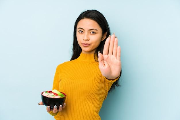 麺を保持している若い中国人女性は混乱し、疑わしく不安を感じています。