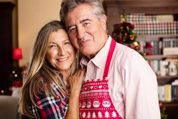 シニアカップルがクリスマスに一緒にポーズを取ります