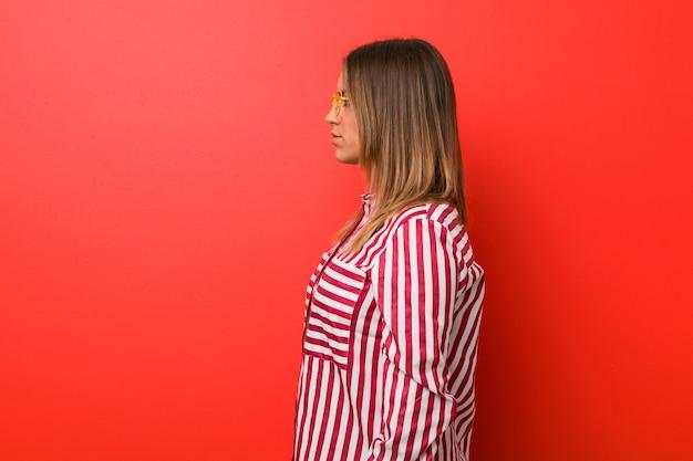 Молодая настоящая харизматичная женщина с реальными людьми смотрит на стену