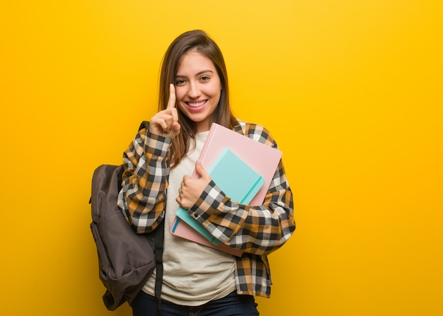ナンバーワンを示す若い学生女性