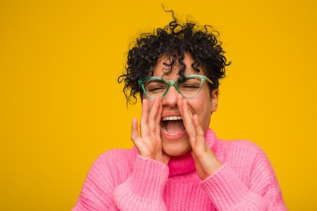 叫んでいるピンクのセーターを着ている若いアフリカ系アメリカ人女性は前に興奮しています。