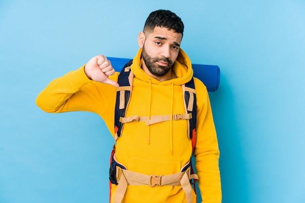 Молодой аравийский путешественник рюкзаком человек показывает жест неприязни, пальцы вниз