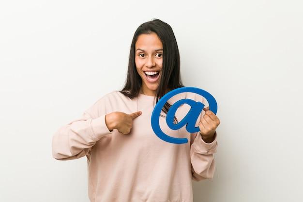 アイコンを保持している若いヒスパニック系女性は、自分自身を指して驚いて、広く笑っています。