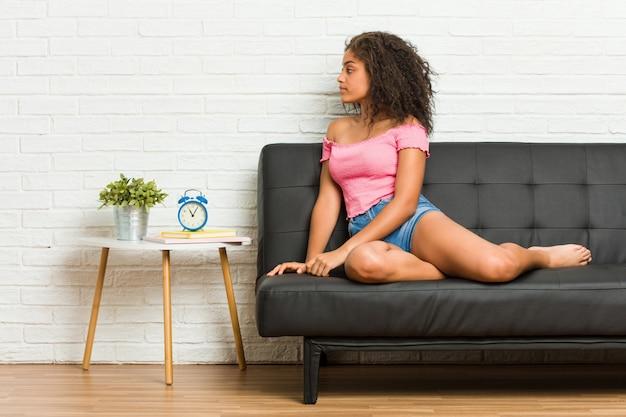 Молодая афро-американская женщина сидя на софе смотря левую