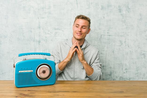 Молодой кавказский человек слушая к радио составляя план в разуме, настраивая идею.