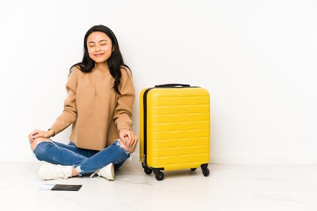 Молодая китайская женщина-путешественница, сидящая на полу с чемоданом, смеется и закрывает глаза