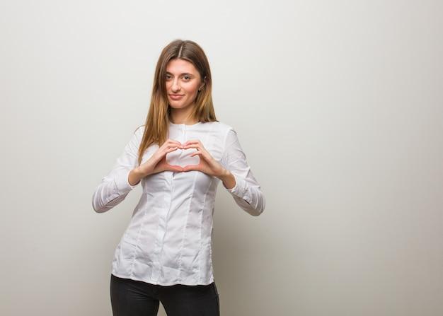 手で心臓の形をしているロシアの少女