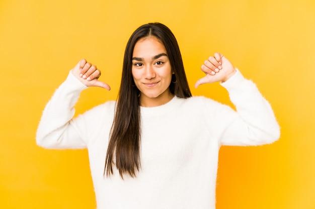 黄色の壁の若い女性は誇りに思って、自信を持って