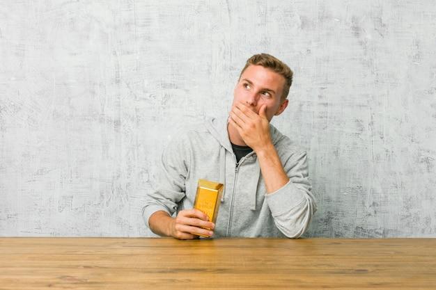 手で口を覆っている空白を探している思慮深いテーブルに金塊を保持している若いハンサムな男。