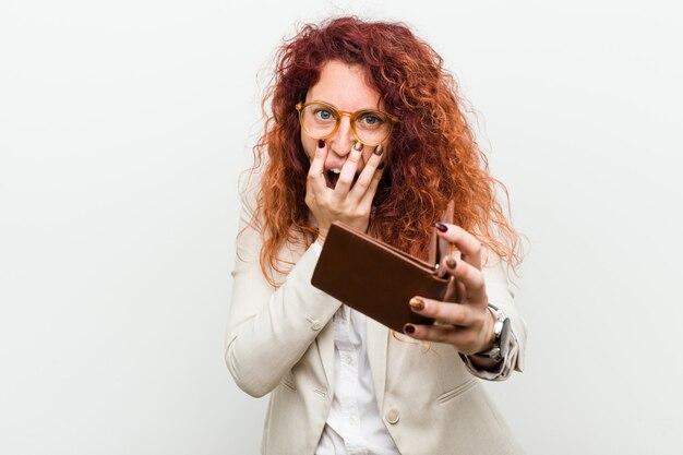 叫んでいる財布を保持している若い白人赤毛の女性は前に興奮しています。