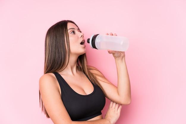 水のボトルを保持している若い白人のスポーティな女性