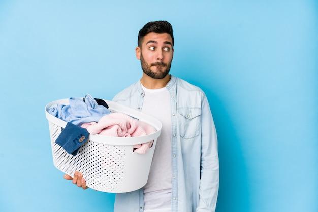 洗濯をしている若いハンサムな男は混乱し、疑念と不安を感じています。