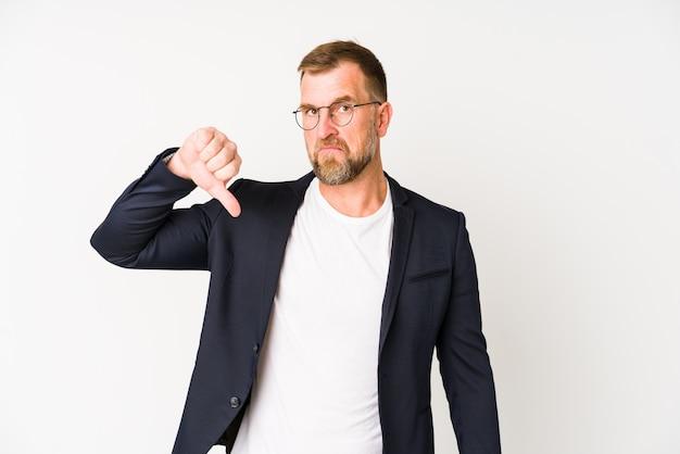 嫌いなジェスチャー、親指ダウンを示す白い壁にシニアビジネス男