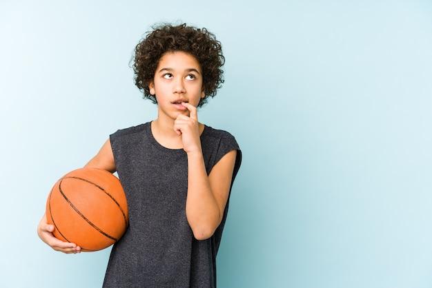 Мальчик ребенк играя баскетбол на голубой стене ослабил думать о что-то смотря пустое пространство.