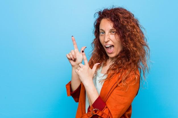 興奮と欲望を表現する空白を指す人差し指で指している若い赤毛のエレガントな女性。