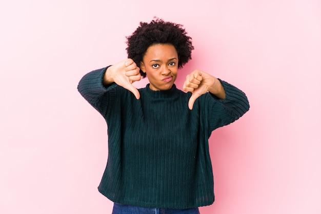 親指ダウンを示すと嫌悪感を表現する分離されたピンクの壁の女性