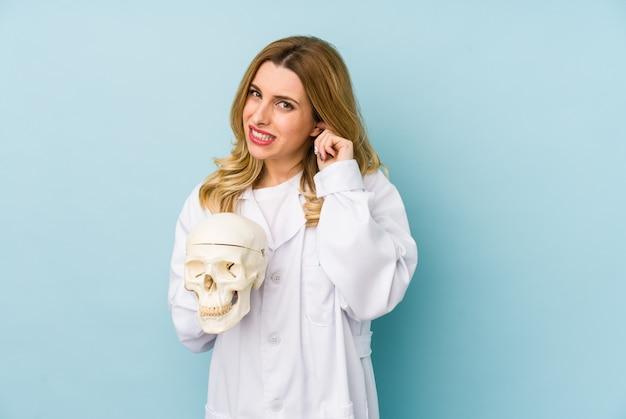 手で耳を覆う分離された頭蓋骨を保持している若い医者女性