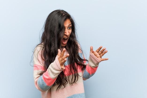 Молодая модная женщина кричит громко, держит глаза открытыми и руки напряжены