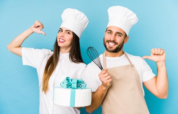 Молодая пара, приготовление торта вместе изолированных счастливых, улыбающихся и веселых